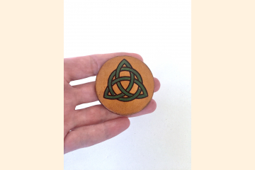 Green Triquetra Magnet held palm side with three fingers to show scale