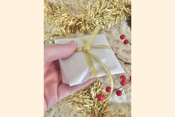 Leather Magnet Gift wrapped Shown in Hand for Scale with Holiday Background